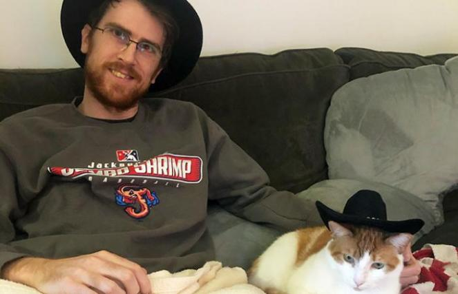 Man wearing a black hat sitting on a couch next to Levi the cat who is wearing a matching black hat