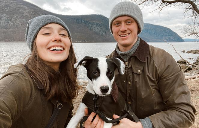 Porter the puppy outside with his two adopters with some water and a hill in the background