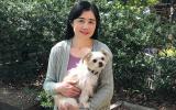 Volunteer Kyoko Bruguera holding a small fluffy white dog