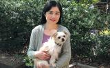 Volunteer Kyoko Bruguera holding a small fluffy white dog
