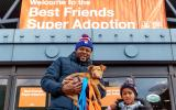 Man holding a puppy he'd adopted, next to his child, in front of a Best Friends Super Adoption banner