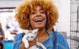 Smiling woman holding a white kitten with a gray spot on his head